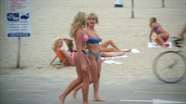 ms pan two girls in bikini walking on sand of beach - 1987 stock-videos und b-roll-filmmaterial