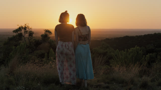 ws slo mo. two girls in flowing dresses watch sunset over valley from green mountainside. - female friendship stock videos & royalty-free footage