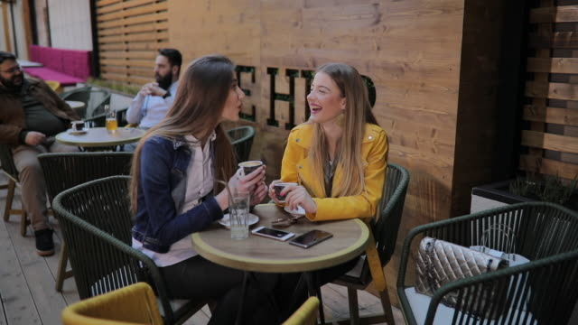 two girls in good mood drinking coffee outdoor in cafe - pavement stock videos & royalty-free footage