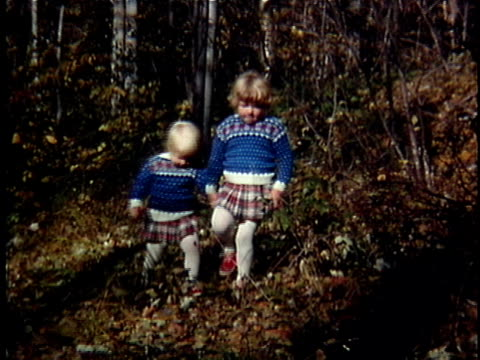 1963 ms pan two girls in matching outfits walk through woods holding hands, vermont, usa - matching outfits stock videos & royalty-free footage