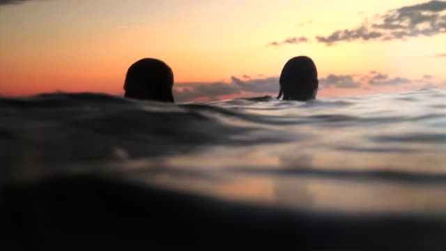 Two girls in the ocean at sunset