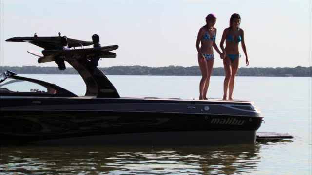 ws two girls jumping off back of boat into lake/ texas - stehendes gewässer stock-videos und b-roll-filmmaterial