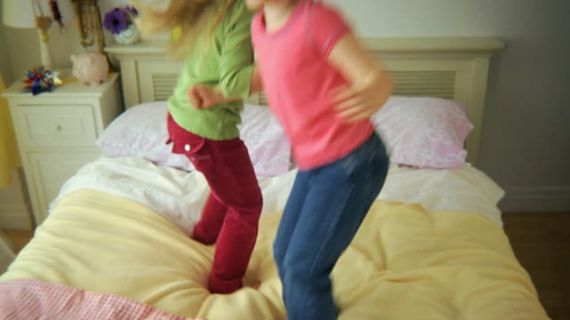 ms tu td two girls (5-6) jumping on bed together / jersey city, new jersey, usa - moving down stock videos & royalty-free footage