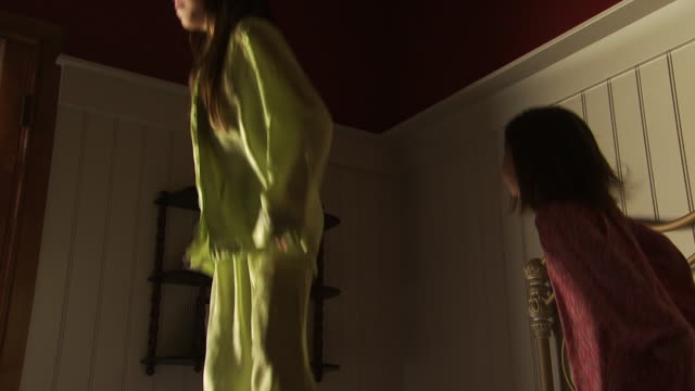 Two girls jumping on bed