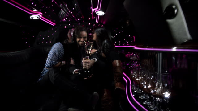 Two girls kiss celebrity award-winner celebrating in back of limousine at awards show