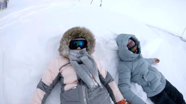 vídeos de stock e filmes b-roll de two girls laying at snowfield - roupa de esqui