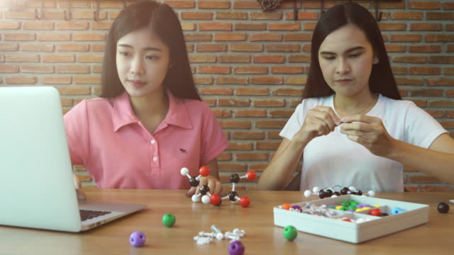 two girls learning on chemistry subject - atom stock videos & royalty-free footage