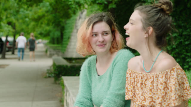 ms. two girls look at smartphone and laugh sitting on stone wall on city sidewalk. - sitting stock videos & royalty-free footage