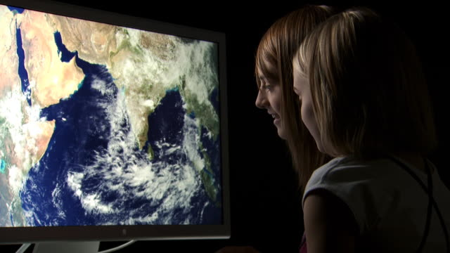 two girls looking at earth on computer monitor - see other clips from this shoot 1167 stock videos and b-roll footage