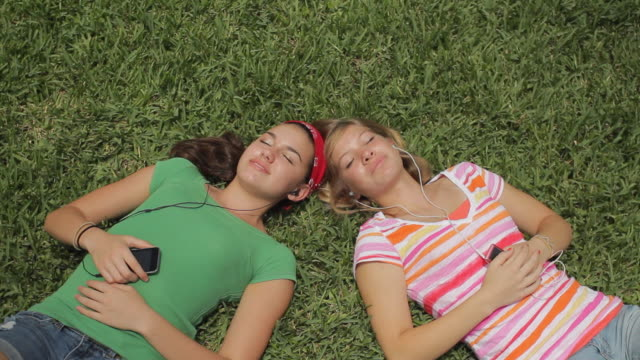 ms ha td two girls (14-15) lying in grass listening to music / cape coral, florida, usa - cape coral stock videos & royalty-free footage