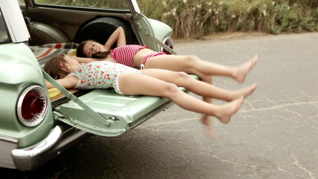 Two girls lying on car, kicking legs