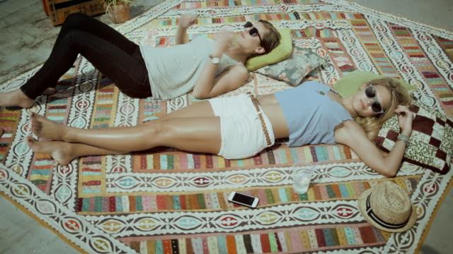 vídeos de stock, filmes e b-roll de duas meninas deitado no tapete - bronzeado