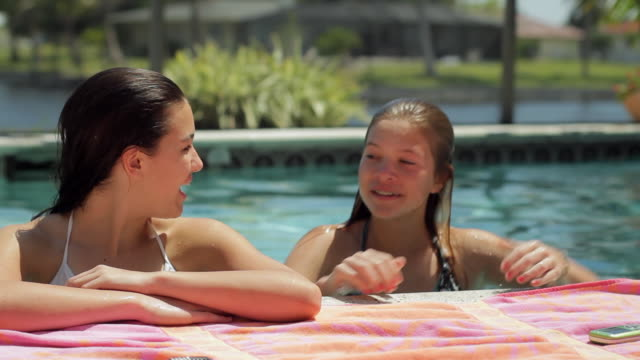 ms two girls (14-15) on edge of swimming pool reading text messages / cape coral, florida, usa - 14 15 years stock videos and b-roll footage