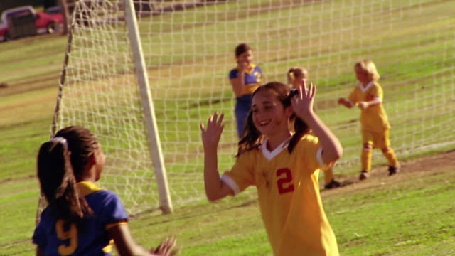 ms pan two girls on opposite soccer teams running towards each other + high fiving with both hands - lega sportiva amatoriale video stock e b–roll