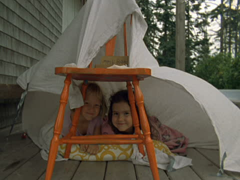 ms two girls on porch in fort made with chair and sheet/ vinalhaven, maine - bettbezug stock-videos und b-roll-filmmaterial