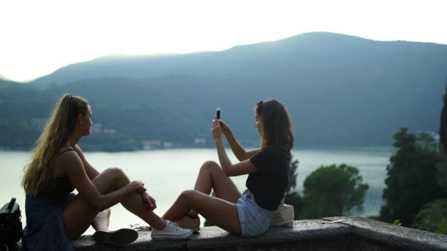two girls on stone wall taking pictures with smartphone, view of lake and mountains below - stone wall stock videos & royalty-free footage