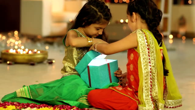 MS Two girls opening gift box and smiling in diwali festival
