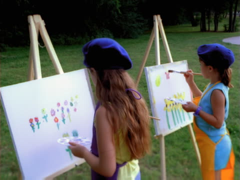 vídeos de stock, filmes e b-roll de two girls painting in the park. - boina