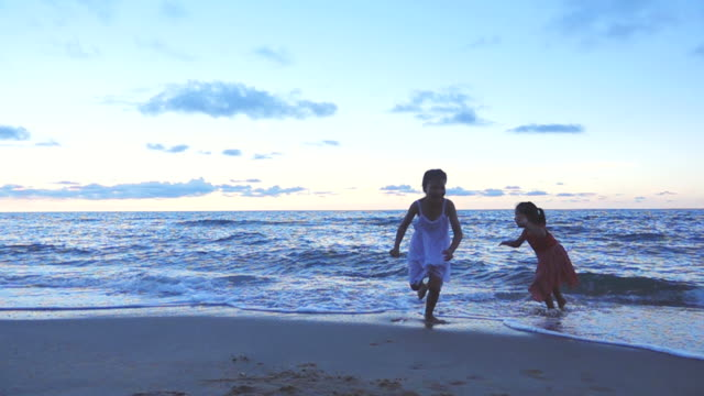 two girls playing and running on the beach, slow motion - children only stock videos & royalty-free footage