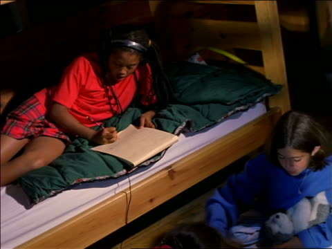 Two girls playing checkers on floor of cabin while other girl on bunk bed with headphones is drawing