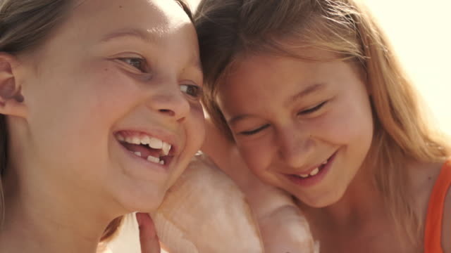 two girls playing on beach listening to conch shell. - seashell stock videos and b-roll footage