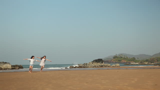 Two girls playing on the beach with her arms outstretched
