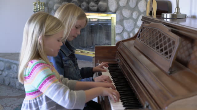 MS two girls playing piano together at home