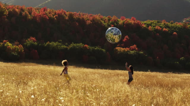 WS Two girls (12-17) playing with inflatable globe ball in field of grass / South Fork, Utah, USA
