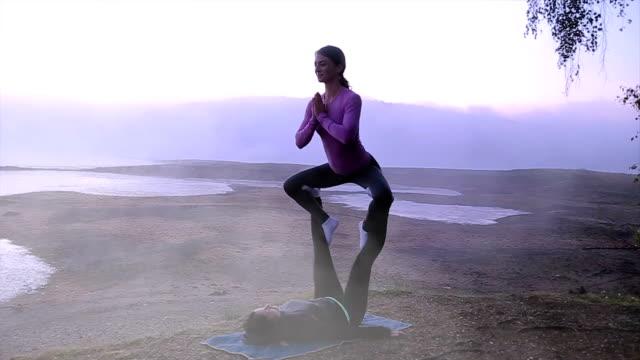 vídeos y material grabado en eventos de stock de dos chicas practican yoga junto a un hermoso lago brumoso - pilates