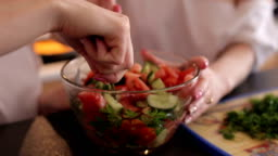 Two girls prepare a vegetable salad in the kitchen