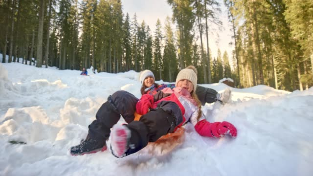 vidéos et rushes de slo mo deux filles leurs luges en plastique vers le bas d'une colline enneigée d'équitation et de rire - low angle view