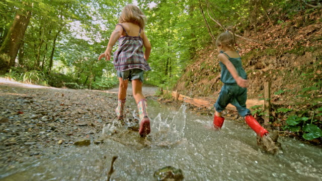 slo mo two girls running across a creek in the forest wearing rain boots - wellington boot stock videos & royalty-free footage