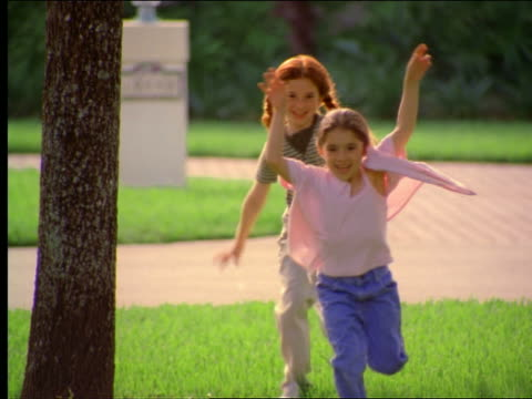 two girls running on grass with driveway in background - childhood stock videos & royalty-free footage