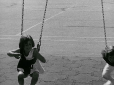 vídeos de stock, filmes e b-roll de two girls running toward into soft seat swings swinging on stomachs tu ms young girl moving hand over hand on monkey bars girls playing on bars meet... - jungle gym