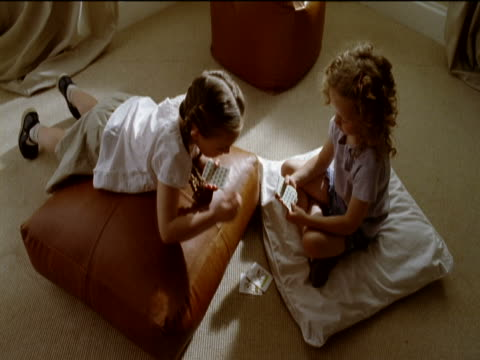 vídeos de stock e filmes b-roll de two girls sat on cushions in a lounge, playing a card game - carta de baralho