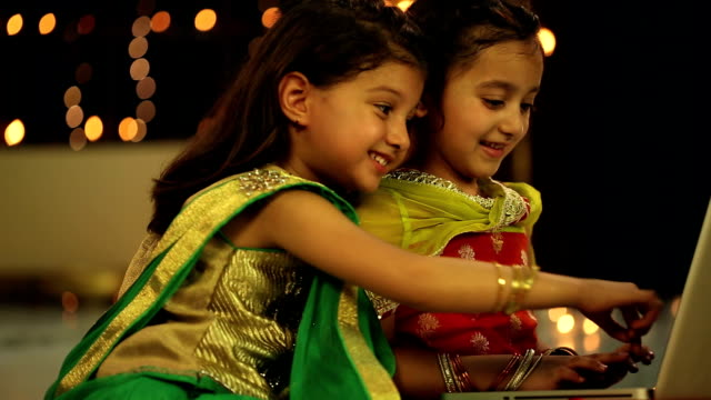 MS Two girls sitting and using laptop in diwali festival