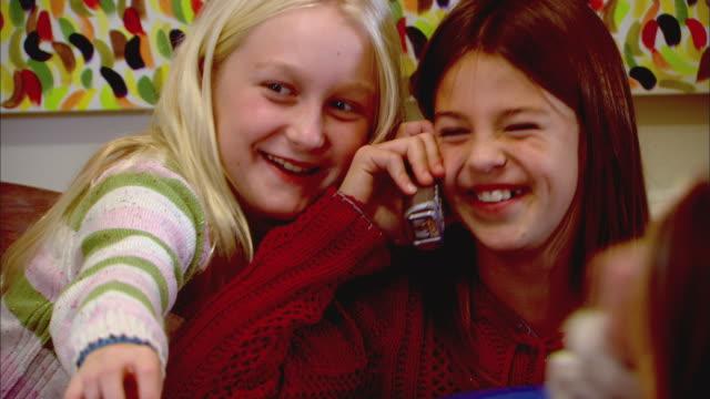 vídeos y material grabado en eventos de stock de cu, two girls (10-11) sitting at table and fooling around, one talking on phone - teléfono sin cable