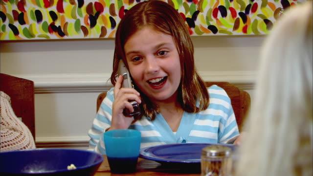 vidéos et rushes de cu, two girls (10-11) sitting at table and talking on phone - téléphone sans fil