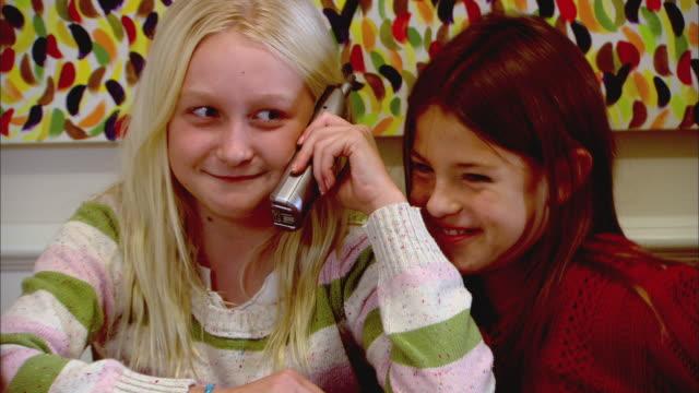 vidéos et rushes de zi, cu, two girls (10-11) sitting at table, one talking on phone - téléphone sans fil