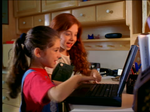Two girls sitting in front of laptop computer punching keys +pointing at screen