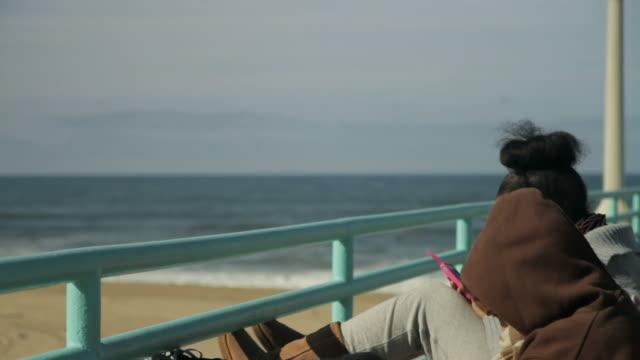 vídeos de stock e filmes b-roll de two girls sitting on bench on pier looking at their phones - só meninas adolescentes