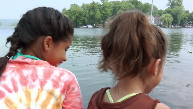 Two girls sitting on dock on lake whispering secrets into each others ears / New Jersey