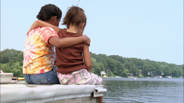 vídeos y material grabado en eventos de stock de two girls sitting on end of dock on lake with arms around each other and fishing / new jersey - brazo sobre el hombro
