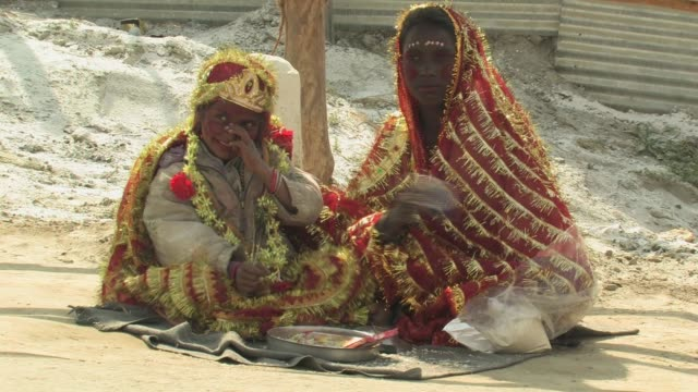 MS, Two girls (10-11, 12-13) sitting on side of road begging for money, people walking in front of camera, Allahabad, Uttar Pradesh, India