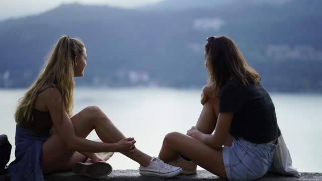 two girls sitting on stone wall overlooking lake and mountains - surrounding wall stock videos & royalty-free footage