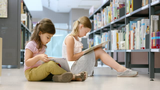 ds two girls sitting on the floor in a public library and reading - sitting on floor stock videos & royalty-free footage
