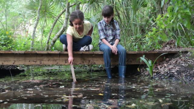 vídeos de stock e filmes b-roll de two girls sitting on wooden bridge in woods - pequeno lago