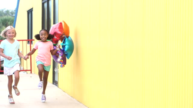 two girls skipping by with balloons, holding hands - skipping along stock videos & royalty-free footage