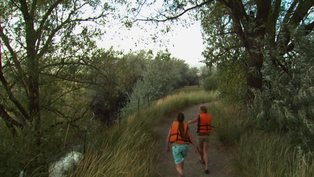 two girls skipping down a trail with life vests - see other clips from this shoot 1171 stock videos and b-roll footage
