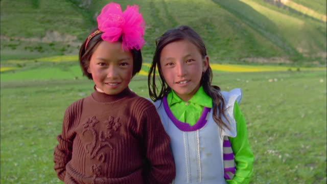 vídeos y material grabado en eventos de stock de two girls smile into camera, himalayas available in hd. - cinta de cabeza